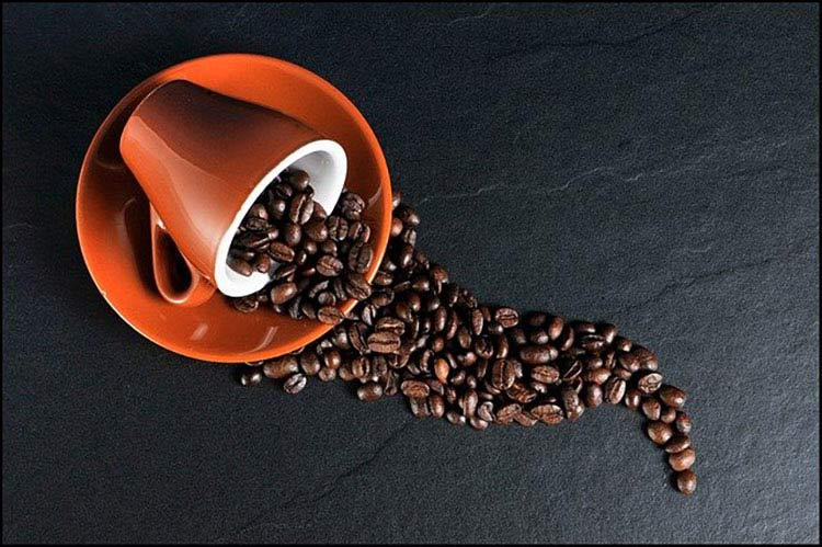coffee beans spilling from orange cup